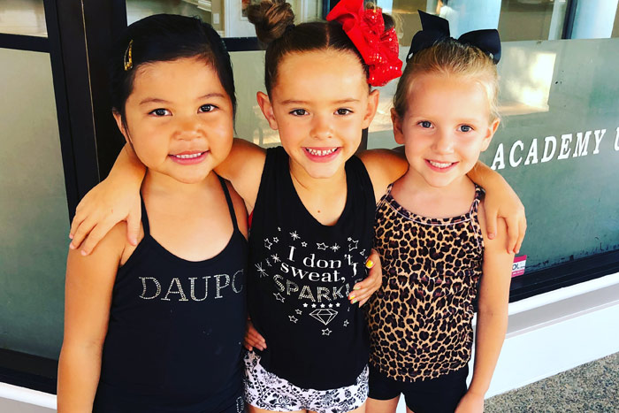 three girls smiling outside of dance studio